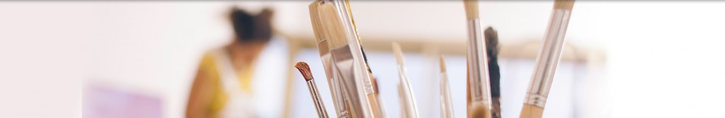 Paintbrushes with out of focus artist in the background