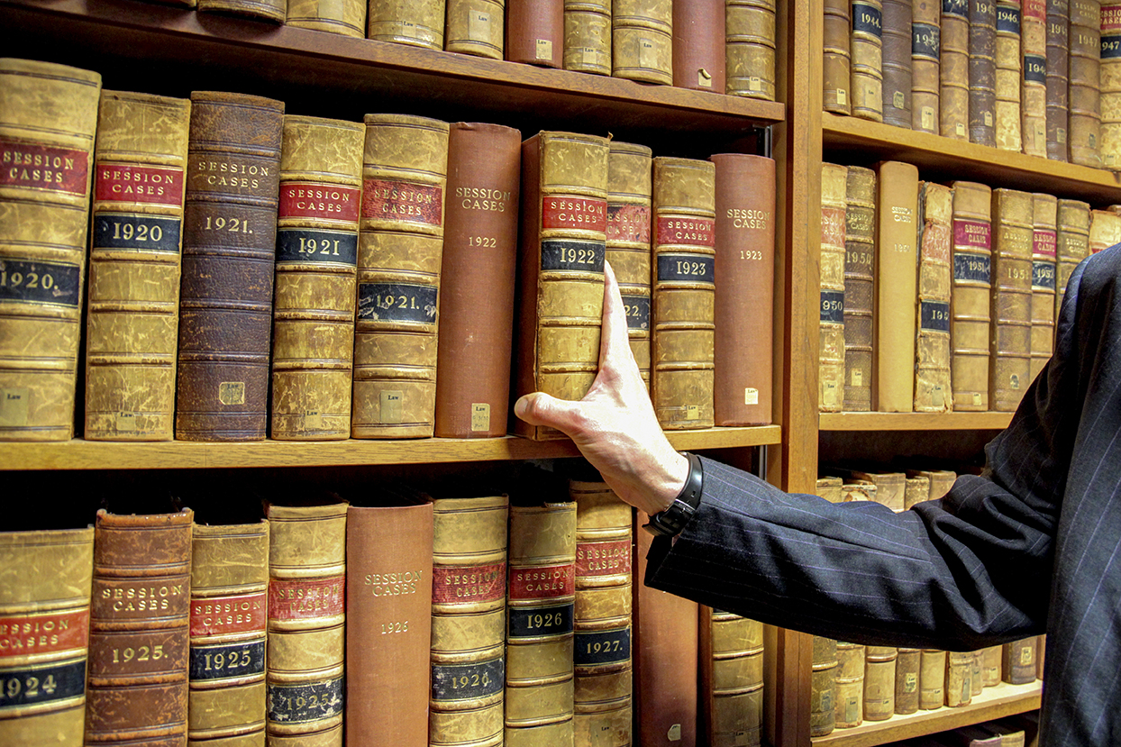 Hand removing legal text from library shelf