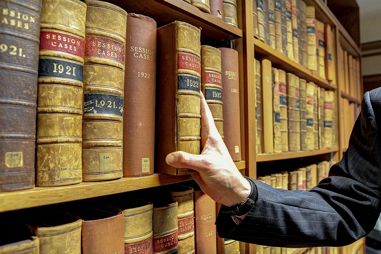 Hand removing legal text from library shelf Graduate Trainee Accountant Vacancy