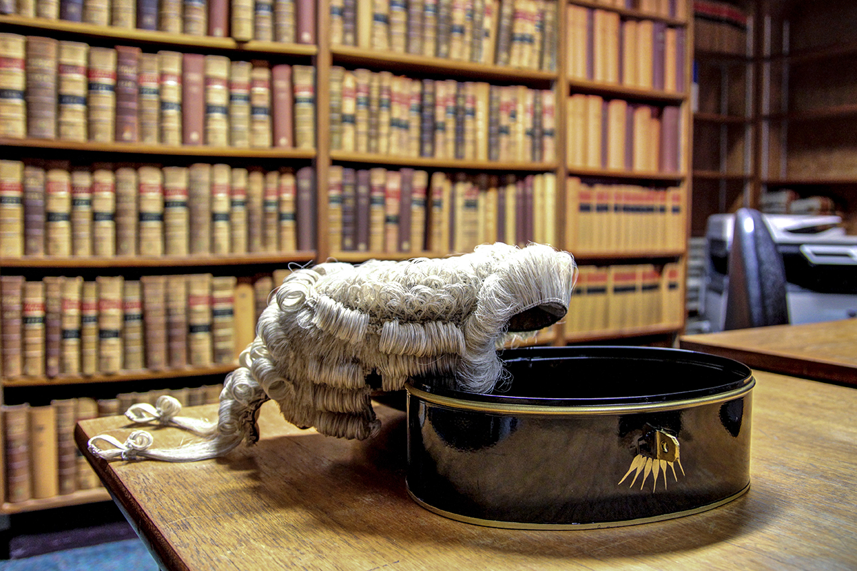 Advocate's wig on tin with library in background